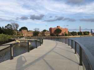 Raised pedestrian trail over the river with Lathrop Homes in the background.